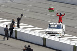 Ross Chastain, right, stands on his car after winning a NASCAR Truck Series auto race as teammates throw an inflatable watermelon onto the track, Saturday, July 27, 2019, in Long Pond, Pa. (AP Photo/Derik Hamilton)