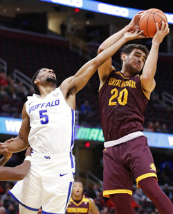 Central Michigan's Kevin McKay (20) grabs a rebound ahead of Buffalo's CJ Massinburg (5) during the first half of an NCAA college basketball game in the semifinals of the Mid-American Conference men's tournament Friday, March 15, 2019, in Cleveland. (AP Photo/Tony Dejak)