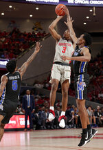 Houston guard Armoni Brooks (3) puts up a three point shot between Memphis guard Kareem Brewton Jr. (5) and Memphis guard Jeremiah Martin, right, during the second half of an NCAA college basketball game Sunday, Jan. 6, 2019, in Houston. (AP Photo/Michael Wyke)