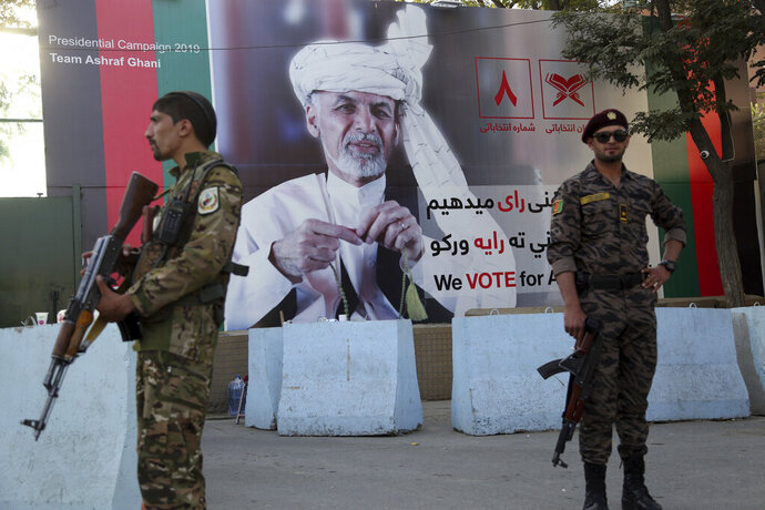 In this Monday, Sept. 23, 2019 photo, Afghan security forces stand guard in front of an election poster for presidential candidate Ashraf Ghani in Kabul, Afghanistan. Millions of Afghans are expected to go to the polls on Saturday to elect a new president, despite an upsurge of violence in the weeks since the collapse of a U.S.-Taliban deal to end America's longest war, and the Taliban warning voters to say away from the polls. (AP Photo/Rahmat Gul)