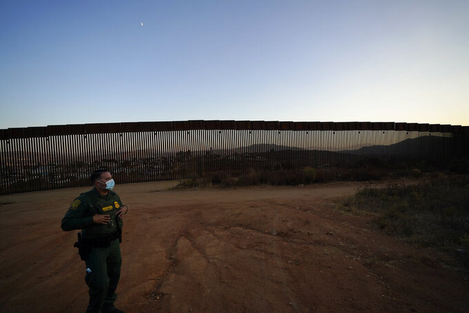Border Patrol agent Justin Castrejon looks out along newly replaced border wall sections Thursday, Sept. 24, 2020, near Tecate, Calif. Top Trump administration officials will visit South Texas five days before Election Day to announce they have completed 400 miles of U.S.-Mexico border wall, attempting to show progress on perhaps the president's best-known campaign promise four years ago. But most of the wall went up in areas that already had smaller barriers. (AP Photo/Gregory Bull)