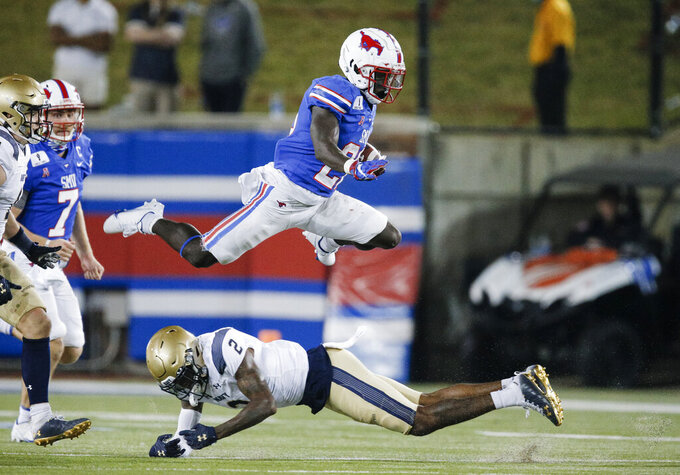 SMU running back Ulysses Bentley IV (26) leaps over Navy cornerback Marcus Wiggins (2) during the second half of an NCAA college football game Saturday, Oct. 31, 2020, in Dallas. (AP Photo/Brandon Wade)