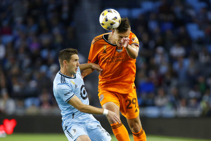 Houston Dynamo defender Sam Junqua (29) heads the ball in front of Minnesota United midfielder Ethan Finlay (13) during the first half of an MLS soccer match, Saturday, Sept. 25, 2021, in St. Paul, Minn. (AP Photo/Andy Clayton-King)