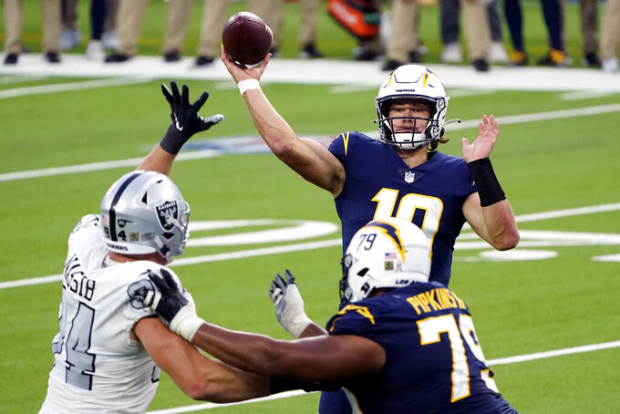 FILE - In this Sunday, Nov. 8, 2020, file photo, Los Angeles Chargers quarterback Justin Herbert throws the ball over Las Vegas Raiders defensive end Carl Nassib, left, and offensive tackle Trey Pipkins during the second half of an NFL football game, in Inglewood, Calif. There's no shortage of high draft picks making huge impact around the league, especially on offense with the instant success of players like Herbert. (AP Photo/Alex Gallardo, File)