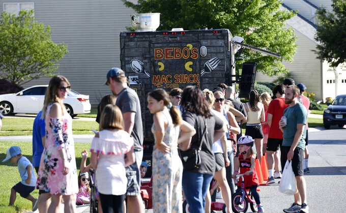 In this Thursday, June 18, 2020, photo, diners line up to patronize Bebo's Mac Shack, a food truck parked on the street in a suburban neighborhood in Eldersburg, Md. Christopher Coil runs Bebo's Mac Shack with his wife, Katie, out of Westminster Riding Club. His menu is devoted to macaroni and cheese dishes, and the food truck itself is colorful, which Coil said makes them stand out a bit. (Dylan Slagle/The Baltimore Sun via AP)