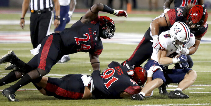 Arizona running back Drake Anderson (8) gets swarmed behind the line of scrimmage by San Diego State linebacker Segun Olubi (24), left, defensive lineman Kahi Neves (91) and defensive lineman Jonah Tavai (66) in the second half of the NCAA college football game in Tucson, Ariz., Saturday, Sept. 11, 2021. (Kelly Presnell/Arizona Daily Star via AP)