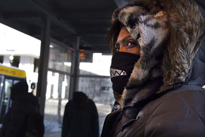 Miyoshi Bradford is bundled up for bitter cold subzero temperatures and wind chills as she waits for a bus in St. Paul, Minn. to take her to her nursing job on Thursday, Feb. 13, 2020. (Jean Pieri/Pioneer Press via AP)