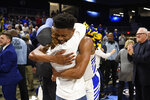 Hofstra guard Eli Pemberton, right, hugs a fan after the team's NCAA college basketball game against Northeastern for the championship of the Colonial Athletic Association men's tournament Tuesday, March 10, 2020, in Washington. Hofstra won 70-61. (AP Photo/Nick Wass)