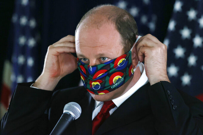 FILE—In this Thursday, May 28, 2020, file photograph, Colorado Governor Jared Polis puts on his face mask after a news conference about the state's efforts against the new coronavirus in Denver. During a news conference Tuesday, June 2, 2020, Polis said that the state is adding more than 800 new contact tracers to Colorado's coronavirus testing effort. (AP Photo/David Zalubowski, File)