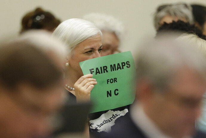 FILE - In this July 26, 2017, file photo, a member of the gallery tries to display her sign while lawmakers convene during a joint select committee meeting on redistricting in Raleigh, N.C. Republican wins in state legislatures in 2010 put them in a commanding position to draw legislative and congressional maps the following year that essentially cemented their political power for a decade.  (AP Photo/Gerry Broome, File)