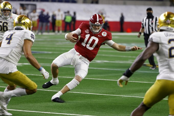 Alabama quarterback Mac Jones runs the ball as Notre Dame cornerback Nick McCloud (4) and Ovie Oghoufo, right, close in to make the stop in the second half of the Rose Bowl NCAA college football game in Arlington, Texas, Friday, Jan. 1, 2021. (AP Photo/Ron Jenkins)