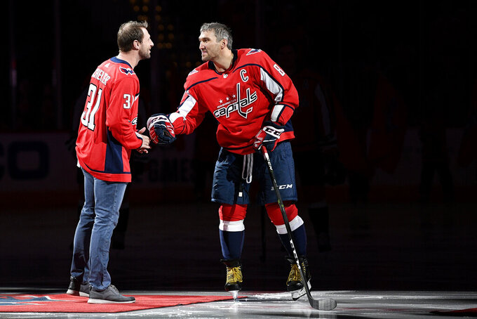 Washington Nationals baseball player Max Scherzer, left, meets with Washington Capitals left wing Alex Ovechkin (8), of Russia, after a ceremonial puck drop before an NHL hockey game between the Capitals and the New York Rangers, Friday, Oct. 18, 2019, in Washington. Scherzer substituted a baseball for a puck. (AP Photo/Nick Wass)