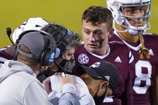 Mississippi State head coach Mike Leach, left, confers with quarterback Will Rogers (2), right, while assistants listen during the second half of an NCAA college football game against Vanderbilt in Starkville, Miss., Saturday, Nov. 7, 2020. (AP Photo/Rogelio V. Solis)