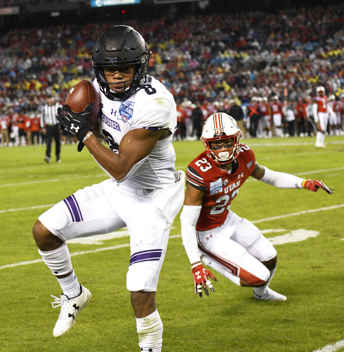 Northwestern wide receiver Kyric McGowan (8) makes a catch in front of the defense of Utah defensive back Julian Blackmon (23) during the first half of the Holiday Bowl NCAA college football game Monday, Dec. 31, 2018, in San Diego. (AP Photo/Denis Poroy)