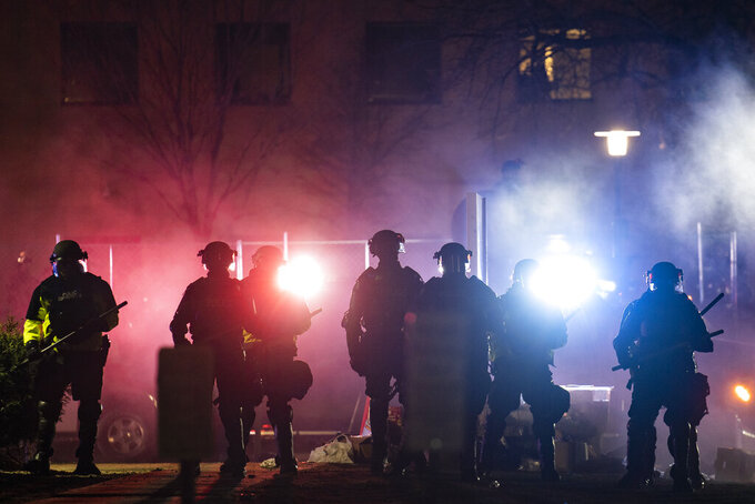 Law enforcement officers clear an area of demonstrators during a protest over Sunday's fatal shooting of Daunte Wright during a traffic stop, outside the Brooklyn Center Police Department on Wednesday, April 14, 2021, in Brooklyn Center, Minn. (AP Photo/John Minchillo)