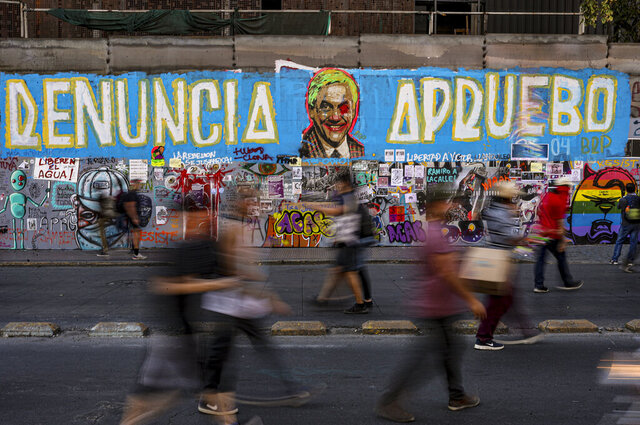 In this March 6, 2020 photo, anti-government protesters walk past a mural denouncing Chile's President Sebastian Pinera in Santiago, Chile. The southern hemisphere summer has come to a close, and Chileans say they fear — or welcome — the prospect that the turn of the season could herald a renewal of the vast protests that shook the nation late last year. (AP Photo/Esteban Felix)