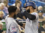 Texas Rangers' Nomar Mazara, right, is met at the dugout after hitting a solo home run during second-inning baseball game action against the Toronto Blue Jays in Toronto, Monday, Aug. 12, 2019. (Fred Thornhill/The Canadian Press via AP)