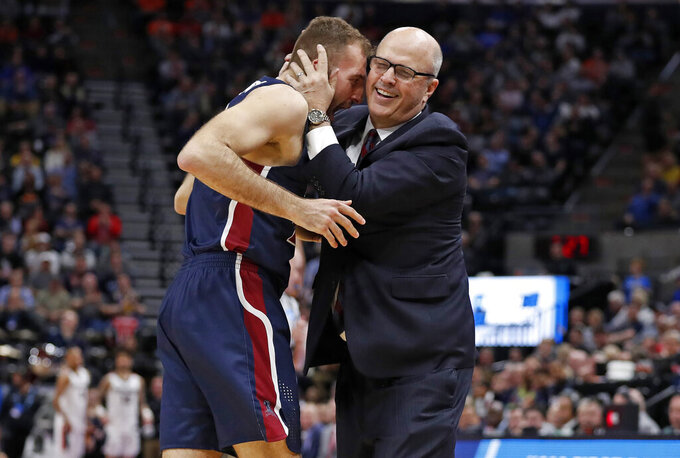 Fairleigh Dickinson forward Nadi Beciri, left, is embraced by coach Greg Herenda after a second-half shot against Gonzaga in a first-round game in the NCAA men's college basketball tournament Thursday, March 21, 2019, in Salt Lake City. (AP Photo/Jeff Swinger)