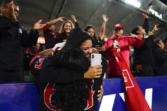 San Diego State offensive lineman Chris Martinez (64) celebrates with a fan after a 33-31 win in triple overtime against Utah in an NCAA college football game Saturday, Sept. 18, 2021, in Carson, Calif. (AP Photo/Ashley Landis)