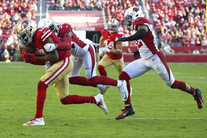 San Francisco 49ers wide receiver Emmanuel Sanders, left, catches a pass against Arizona Cardinals strong safety Jalen Thompson (34) and strong safety Budda Baker (32) during the second half of an NFL football game in Santa Clara, Calif., Sunday, Nov. 17, 2019. (AP Photo/John Hefti)