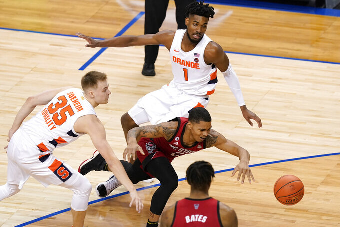 North Carolina State guard Shakeel Moore, right, chases a ball as Syracuse guard Buddy Boeheim (35) and teammate forward Quincy Guerrier (1) defend during the first half of an NCAA college basketball game in the second round of the Atlantic Coast Conference tournament in Greensboro, N.C., Wednesday, March 10, 2021. (AP Photo/Gerry Broome)