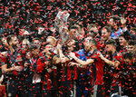 FILE - In this Dec. 8, 2018, file photo, Atlanta United team captain Michael Parkhurst, center, kisses the trophy as teammates celebrate after they defeated the the Portland Timbers 2-0 in the MLS Cup championship soccer game in Atlanta. Atlanta United won 2-0. (AP Photo/Todd Kirkland, File)