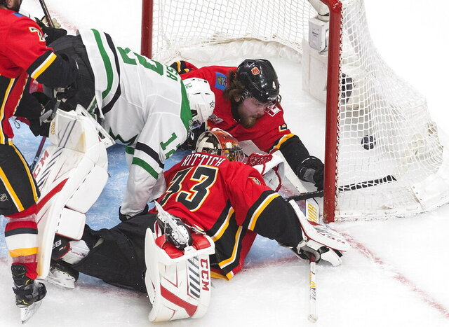 Calgary Flames' Rasmus Andersson (4) and goalie David Rittich try for the puck as Dallas Stars' Radek Faksa (12) puts it into the net during second-period NHL Western Conference Stanley Cup playoff hockey game action in Edmonton, Alberta, Thursday, Aug. 20, 2020. (Jason Franson/The Canadian Press via AP)