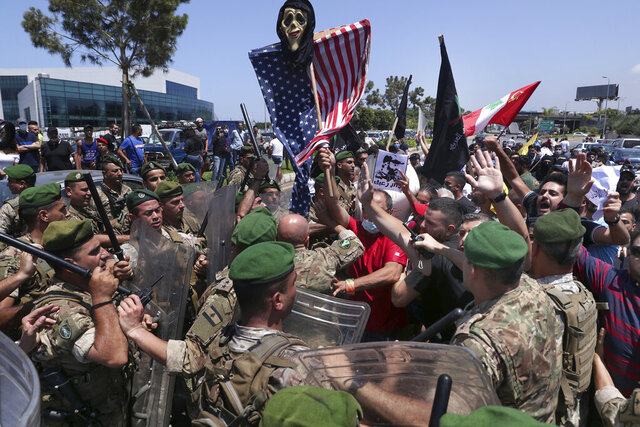 Hezbollah supporters scuffle with Lebanese army soldiers while protesting the visit by Gen. Frank McKenzie, the head of U.S. Central Command, outside the Rafik Hariri International Airport in Beirut, Lebanon, Wednesday, July 8, 2020. (AP Photo/Bilal Hussein)
