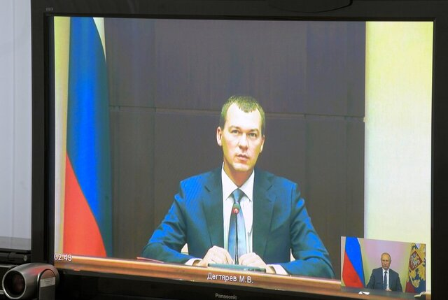 Liberal Democratic Party lawmaker Mikhail Degtyarov is seen on a TV screen during a video conference with Russian President Vladimir Putin in Kerch, Crimea, Monday, July 20, 2020. Russian President Vladimir Putin on Monday appointed lawmaker Mikhail Degtyarov acting governor of the Kharaborvsk region. His predecessor Sergei Furgal was arrested on Murder charges on July 9. Tens of thousands of people have been protesting Furgal's arrest ever since. (Alexei Druzhinin, Sputnik, Kremlin Pool Photo via AP)