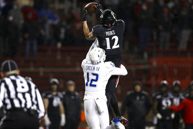 Tulsa cornerback Allie Green IV (12) defends as Cincinnati wide receiver Alec Pierce (12) catches a pass during the first half of the American Athletic Conference championship NCAA college football game, Saturday, Dec. 19, 2020, in Cincinnati. (AP Photo/Aaron Doster)