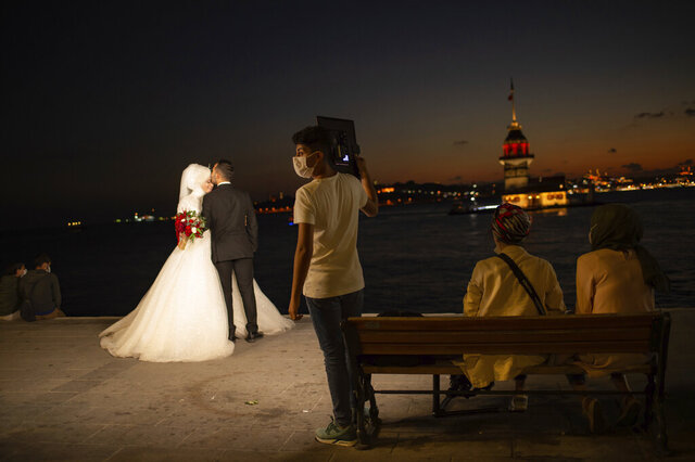 A wedding photographer's assistant, wearing a mask for protection against the spread of coronavirus, holds lighting equipment, as a couple poses for photographs backdropped by Istanbul's iconic Maiden's Tower (Kiz Kulesi) at the Bosphorus Strait separating the European and Asian sides of Istanbul, Friday, Sept. 11, 2020. Turkey is getting tough on people who flout self-isolation rules despite testing positive for the coronavirus. An Interior Ministry circular sent to the country's 81 provinces on Friday said people caught leaving their homes despite isolation orders will be quarantined and supervised at state-owned dormitories or hostels. (AP Photo/Yasin Akgul)