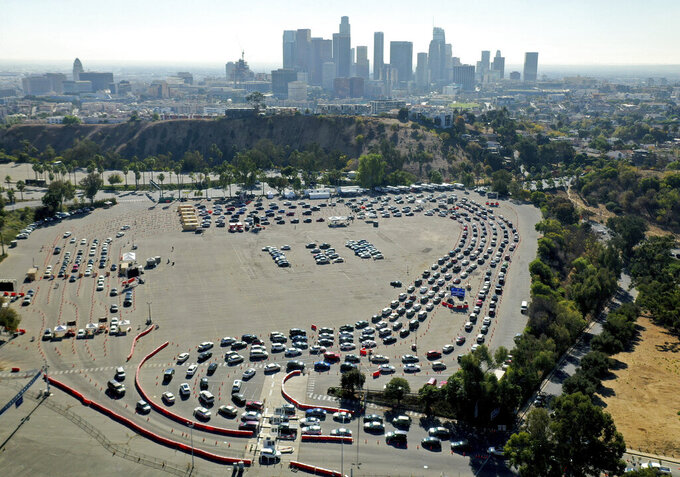 Drivers are in long lines at a COVID-19 testing site in a parking lot at Dodger Stadium on Tuesday, Nov. 17, 2020, in Los Angeles. (Dean Musgrove/The Orange County Register via AP)
