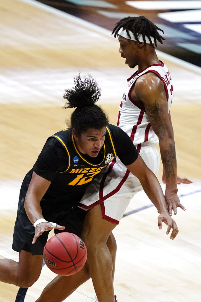 Missouri guard Dru Smith, left, is fouled by Oklahoma guard Alondes Williams, right, during the second half of a first-round game in the NCAA men's college basketball tournament at Lucas Oil Stadium, Saturday, March 20, 2021, in Indianapolis. (AP Photo/Darron Cummings)