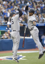 New York Yankees' Aaron Hicks, right, is met by Luke Voit after hitting a three-run home run against the Toronto Blue Jays during the second inning of a baseball game Thursday, June 6, 2019, in Toronto. (Fred Thornhill/The Canadian Press via AP)