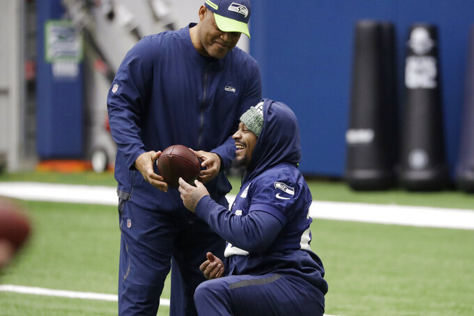 Seattle Seahawks running back Marshawn Lynch, right, talks with defensive coordinator Ken Norton Jr. during warmups at the NFL football team's practice facility Tuesday, Dec. 24, 2019, in Renton, Wash. When Lynch played his last game for the Seahawks in 2016, the idea of him ever wearing a Seahawks uniform again seemed preposterous. Yet, here are the Seahawks getting ready to have Lynch potentially play a major role Sunday against San Francisco with the NFC West title on the line. (AP Photo/Elaine Thompson)