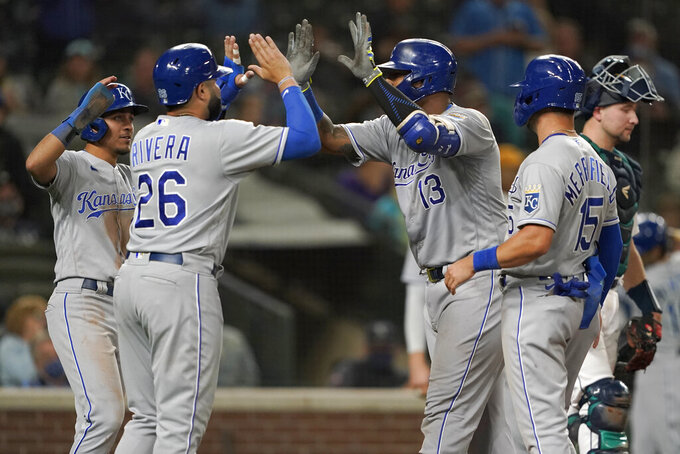 Kansas City Royals' Salvador Perez (13) is greeted at the plate by Emmanuel Rivera (26) after Perez hit a grand slam against the Seattle Mariners during the sixth inning of a baseball game Thursday, Aug. 26, 2021, in Seattle. (AP Photo/Ted S. Warren)