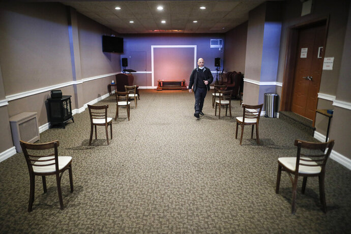 Pat Marmo, owner of Daniel J. Schaefer Funeral Home, walks through a viewing room set up to respect social distancing, Thursday, April 2, 2020, in the Brooklyn borough of New York. He and other funeral directors are seeing a surge of clients because of the coronavirus pandemic. (AP Photo/John Minchillo)