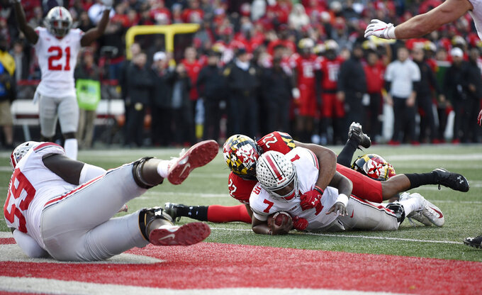 Ohio State quarterback Dwayne Haskins Jr. (7) lies on the end zone after he scored a touchdown during overtime of an NCAA football game against Maryland linebacker Isaiah Davis (22), Saturday, Nov. 17, 2018, in College Park, Md. Ohio State won 52-51 in overtime. (AP Photo/Nick Wass)