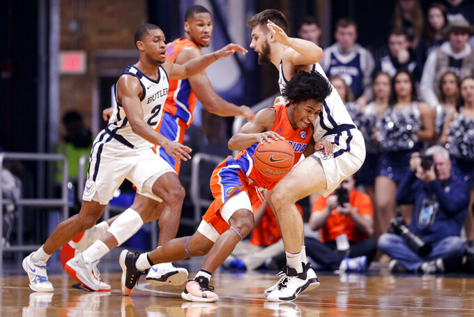 Florida guard Ques Glover (0) drives around Butler forward Bryce Golden (33) in the first half of an NCAA college basketball game in Indianapolis, Saturday, Dec. 7, 2019. (AP Photo/Michael Conroy)