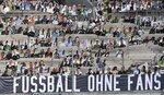 "Thousands of cardboards with photos of Borussia Moechengladbach soccer fans are displayed on the stands at he stadium in Moenchengladbach, Germany, Tuesday, Aug. 4, 2020. A banner reads ""football without fans"". Because of the COVID-19 pandemic, all Bundesliga matches took place behind closed doors. The German football league, DFL, works on a concept for the new season with fans returning to the stadiums. (AP Photo/Martin Meissner)"