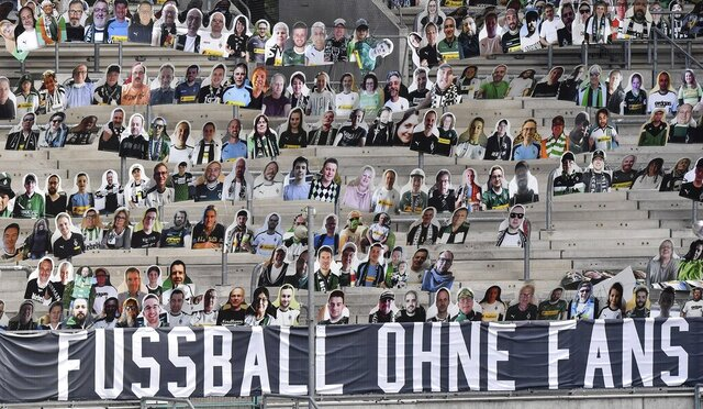 Thousands of cardboards with photos of Borussia Moechengladbach soccer fans are displayed on the stands at he stadium in Moenchengladbach, Germany, Tuesday, Aug. 4, 2020. A banner reads