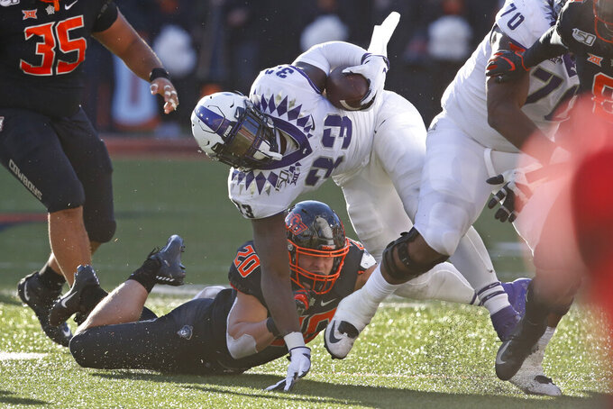 TCU running back Sewo Olonilua (33) is tackled by Oklahoma State's Malcolm Rodriguez (20) in the second half of an NCAA college football game in Stillwater, Okla., Saturday, Nov. 2, 2019. (AP Photo/Sue Ogrocki)