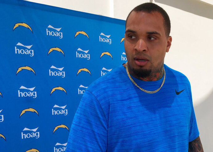 Los Angeles Chargers center Mike Pouncey answers a question after his first workout at his new team's training complex in Costa Mesa, Calif., Monday, April 16, 2018. Pouncey acknowledged he was irritated by the unceremonious manner in which the Miami Dolphins released him during the offseason. (AP Photo/Greg Beacham)