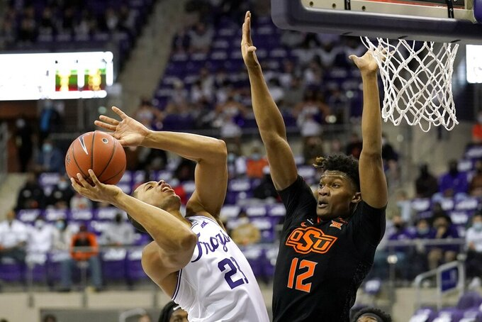 TCU forward Jaedon LeDee (23) shoots as Oklahoma State's Matthew-Alexander Moncrieffe (12) defends during the second half of an NCAA college basketball game in Fort Worth, Texas, Wednesday, Feb. 3, 2021. (AP Photo/Tony Gutierrez)