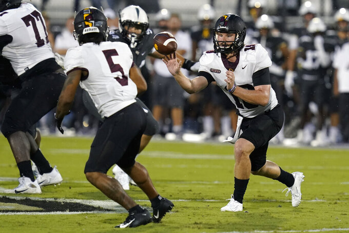 Bethune-Cookman quarterback Shannon Patrick (18) tosses the ball to running back Que'shaun Byrd (5) during the first half of an NCAA college football game against Central Florida, Saturday, Sept. 11, 2021, in Orlando, Fla. (AP Photo/John Raoux)