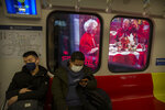 People wear masks on a subway train as it stops near a billboard showing a family having a New Year's banquet meal in Beijing, Friday, Jan. 24, 2020. A virus that has killed more than two dozen people and sickened hundreds more has all but shut down China's biggest holiday of the year, the Lunar New Year. Instead of family reunions or sightseeing trips, many of the country's 1.4-billion people are hunkering down as the country scrambles to prevent the illness from spreading further. (AP Photo/Mark Schiefelbein)