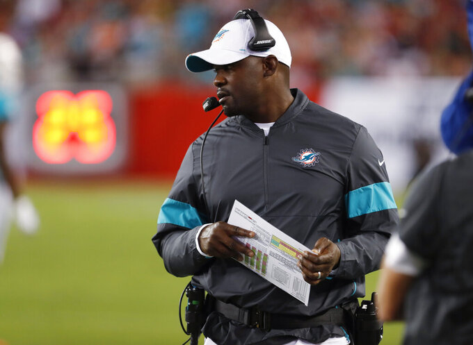 FILE - In this Aug. 16, 2019, file photo, Miami Dolphins coach Brian Flores watches during the first half of the team's NFL preseason football game against the Tampa Bay Buccaneers in Tampa, Fla. First-time head coach Flores faces a tricky task: While he tries to establish a winning culture, the season will be mostly about losing and how the Dolphins position themselves for next year's draft, when they'll likely take a quarterback in the opening round for only the second time since Dan Marino in 1983. (AP Photo/Mark LoMoglio, File)