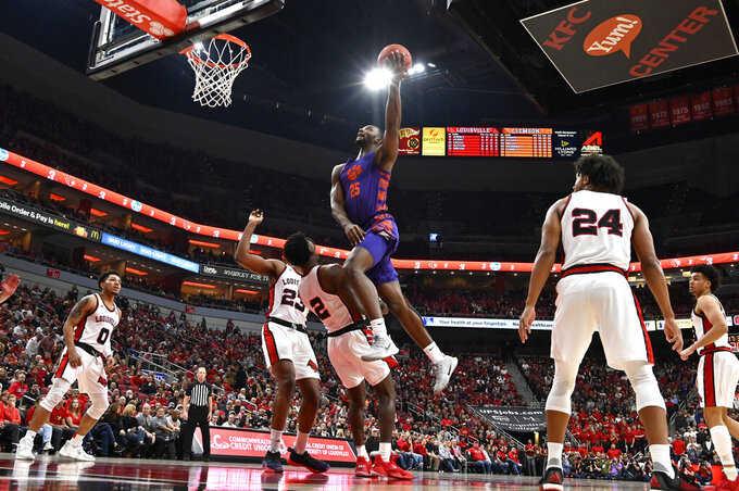 Clemson forward Aamir Simms (25) charges into Louisville guard Darius Perry (2) as he attempts a layup during the first half of an NCAA college basketball game in Louisville, Ky., Saturday, Jan. 25, 2020. (AP Photo/Timothy D. Easley)