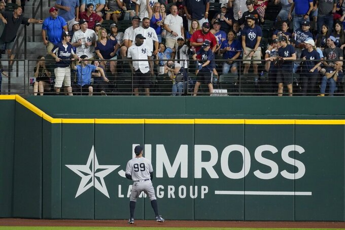 New York Yankees right fielder Aaron Judge (99) looks up to see a young fan catching a Texas Rangers' Adolis Garcia solo home run ball in the second inning of a baseball game in Arlington, Texas, Monday, May 17, 2021. (AP Photo/Tony Gutierrez)