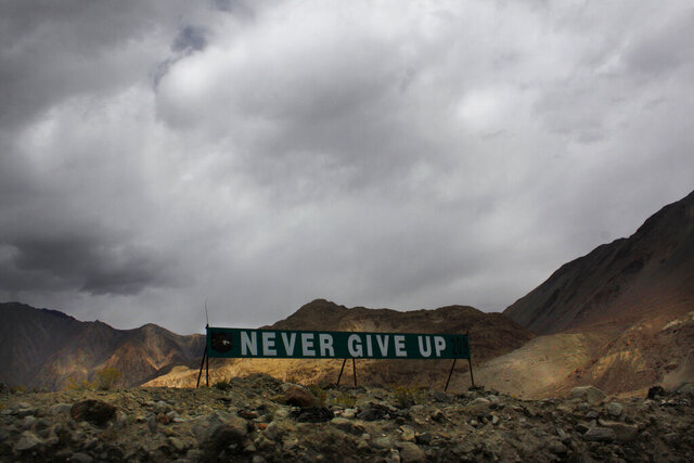 In this Sept. 14, 2017, file photo, a banner erected by the Indian army stands near Pangong Tso lake near the India-China border in India's Ladakh area. As the escalating and bitter military standoff between India and China protracts following their bloodiest confrontation in decades in the Ladakh region in 2020, experts warn the two nuclear-armed countries can unintentionally slide into a war over the roof of the world. The two most populous nations share thousands of kilometers (miles) disputed border and have accused each other for opening new fronts. (AP Photo/Manish Swarup, File)